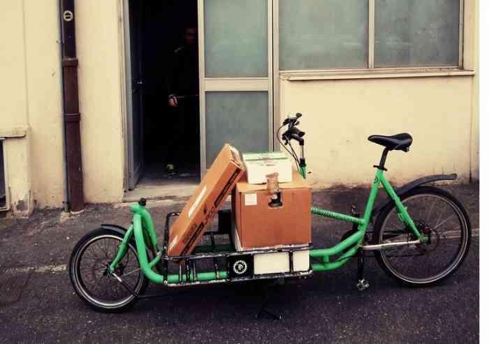 Distribuzione in centro in bicicletta, slogan ecologici ma i mezzi inquinanti rimangono