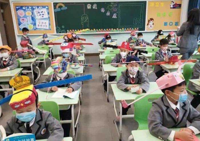 Coronavirus, in Cina bambini creano cappelli anti contagio